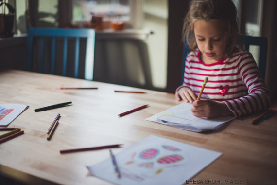 A 7 year old girl is left-handed and is using a pencil for doing homework while seated at a table. She is near windows and there is soft light shining around her.